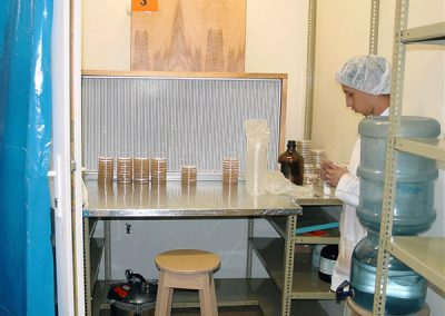 This is a mushroom lab. Note the work surface in front of a HEPA filter through which clean air is blown across the working materials toward the lab worker. Also note the stack of petri dishes.
